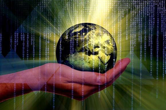A hand holding a globe with code running all over the screen